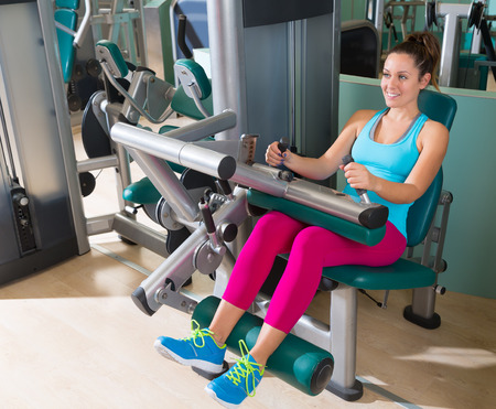 seated: Gym seated leg curl machine exercise woman at indoor Stock Photo