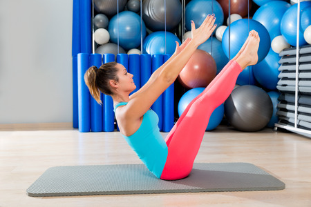 legs open: Pilates Teaser exercise woman on mat gym indoor and swiss balls background