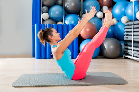 teaser: Pilates Teaser exercise woman on mat gym indoor and swiss balls background