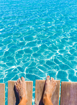 sandy feet: sandy feet on the pier under tropical turquoise water sea ocean Stock Photo