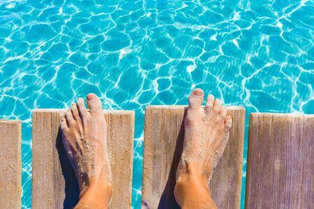 sandy feet: sandy feet on the pier under tropical turquoise water sea ocean Stock Photo