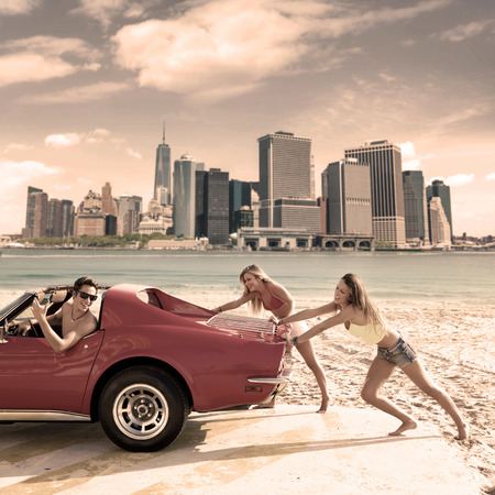 teen beach: Car pushing teen girls humor funny guy driving in Manhattan New York photo mount Stock Photo