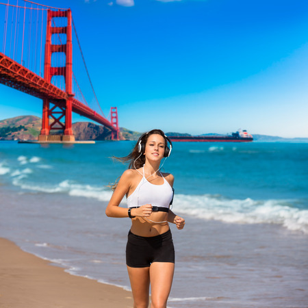 bridge footing: Brunette girl running on the beach San Francisco Golden Gate bridge photo mount Stock Photo