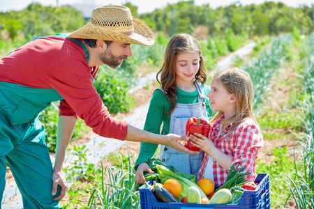 Farmer man blijkt groenten te oogsten voor de gek meisjes in boomgaard Stockfoto