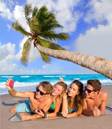 teen bikini: Selfie photo of young friends group in a tropical beach lying on sand