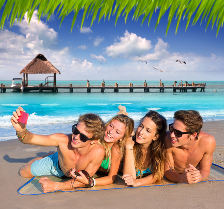 Selfie photo of young friends group in a tropical beach lying on sand photo