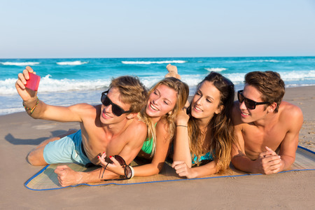 teen girl bikini: Selfie photo of young friends group in a tropical beach lying on sand