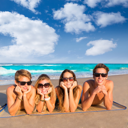 four person: Beach friends together tourits portrait on the sand smiling happy