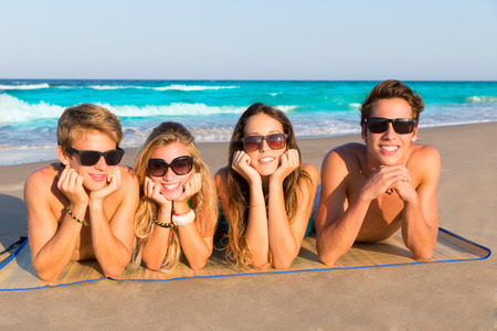 Beach friends together tourits portrait on the sand smiling happy photo