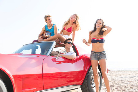 friends group at beach in sports car convertible having fun party with guitar photo