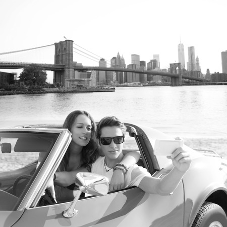 selfie of young teen couple at convertible car in New York Brooklyn Bridge photo mount photo