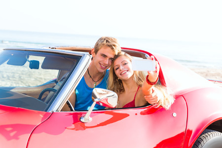 selfie photo of young teen couple in convertible sports car photo
