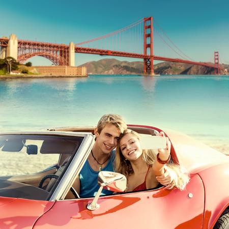 san francisco golden gate bridge: selfie of young teen couple at convertible car in San Francisco Golden Gate Bridge photo mount