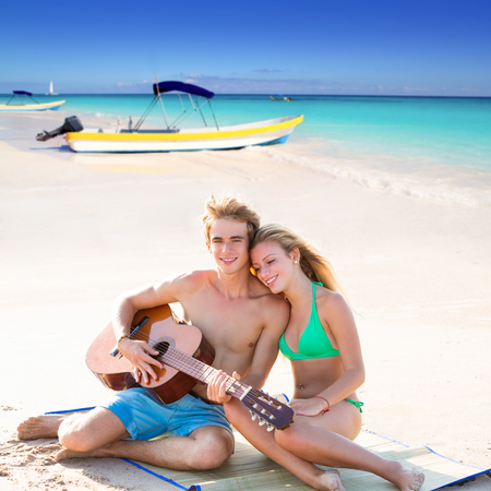 playing in the sea: Blond young tourist couple playing guitar at beach in Mexico Caribbean photo mount Stock Photo