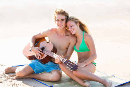 blonde teenage girl: Blond young tourist couple playing guitar at beach Stock Photo