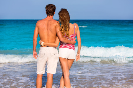 Couple of young tourists in a tropical summer beach rear view hug photo