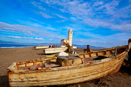 beached: Cabo de Gata in Almeria at San Miguel Beach and Salinas church with stranded boats Stock Photo