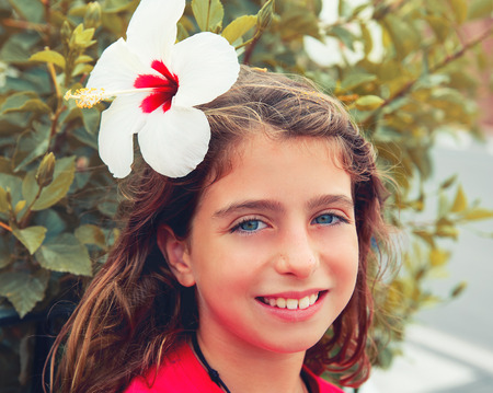 brunette girl: Beautiful kid girl with hibiscus flower in hair blue eyes
