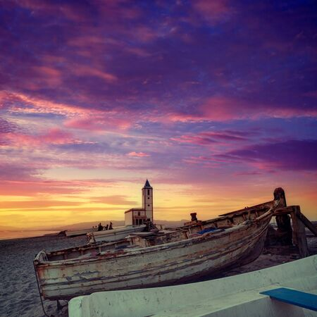 stranded: Cabo de Gata in Almeria at San Miguel Beach and Salinas church with stranded boats at sunset