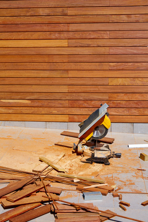 wood panel: Ipe wood fence installation with carpenter table circular saw and sawdust