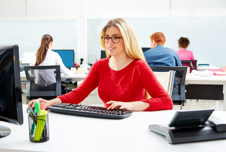 Blond glasses businesswoman working office with computer at desk Stock Photo