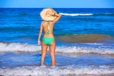 view girl: Girl young standing looking at the sea with beach hat rear back view