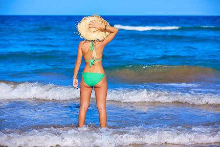 mujer mirando el horizonte: Niña de pie mirando el mar con sombrero de playa trasera vista posterior