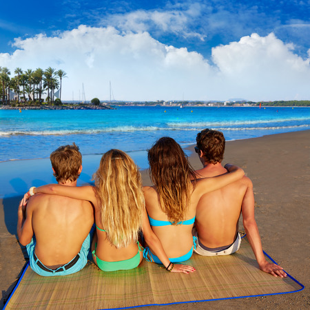 summer holiday bikini: friends group couples sitting in beach sand rear view Alcudia Mallorca photo mount Stock Photo