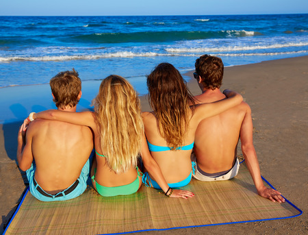 view girl: friends group couples sitting in beach sand rear view back looking to the sea Stock Photo