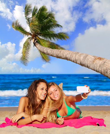 teen girl bikini: happy girl friends selfie portrait beach sand with palm tree photo mount Stock Photo