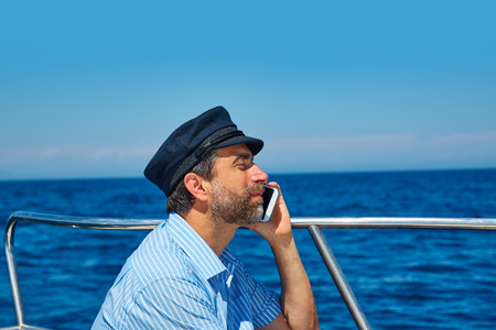 Captain cap sailor man talking mobile phone in boat sailng in the ocean sea