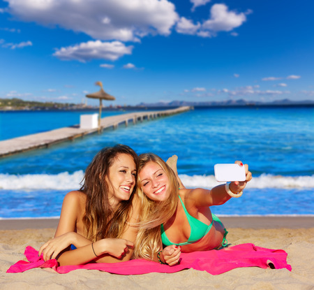 pink bikini: happy girl friends selfie portrait beach sand in Mallorca photo mount