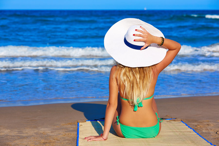 rear view girl: Blond young girl sitting sitting looking sea with beach hat rear back view