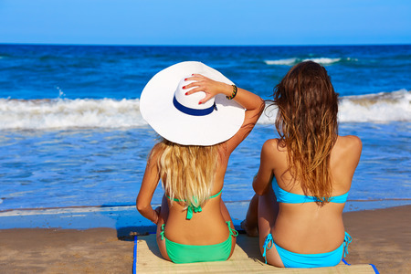 beach blond hair: Beach girls rear back biew sitting in the beach looking horizon in summer