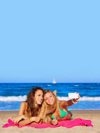 girl with towel: happy girl friends selfie portrait lying on beach sand in summer vacation