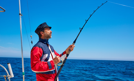 saltwater: Beard sailor man fishing rod trolling in saltwater in a boat trolling with captain cap Stock Photo