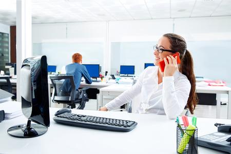personas trabajando en oficina: Brunette gafas de negocios que trabajan en la oficina hablando teléfono inteligente