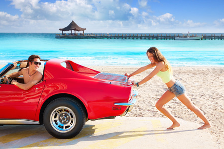Girl pushing a broken car on the tropical beach funny guy photo mount Stock Photo