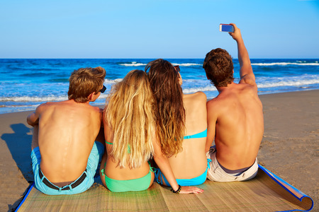 rear view girl: friends group selfie photo sitting in beach sand rear back view Stock Photo