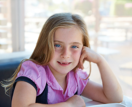 Blond relaxed happy kid girl expression blue eyes smiling