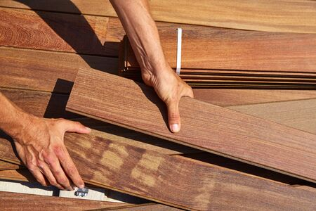 slats: Ipe decking installation with carpenter hands holding tropical wood slats