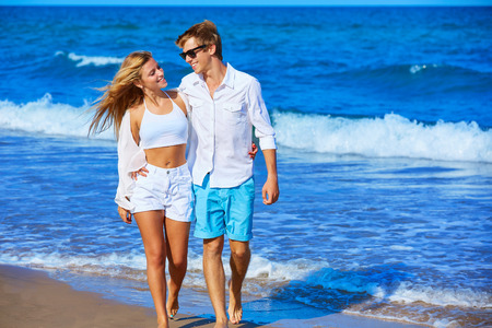 couple nature: Blond young couple walking on the beach shore in summer vacation Stock Photo