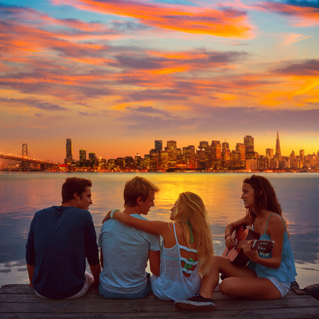 brunette teen: Friends group playing guitar in sunset pier at dusk in San francisco photo mount