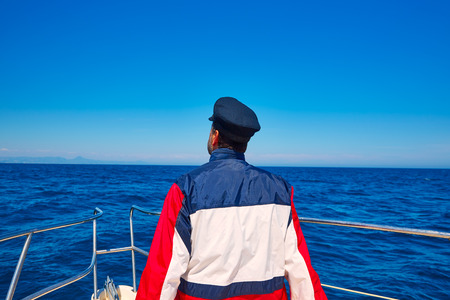 rear sailor man sailing sea ocean in a boat with captain cap looking horizon