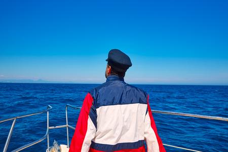 freshwater sailor: rear sailor man sailing sea ocean in a boat with captain cap looking horizon
