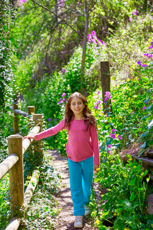 trunk: kid girl in spring track in Cuenca forest of Spain with wooden fence