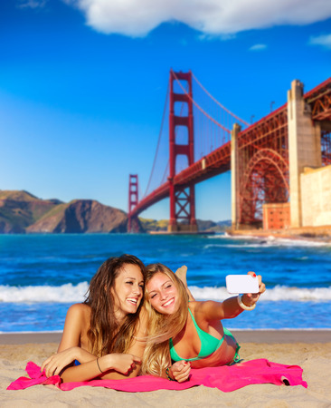 teen bikini: happy girl friends selfie portrait beach sand in San Francisco photo mount