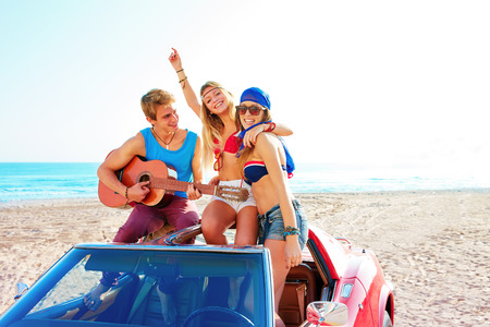 young group having fun on the beach playing guitar and dancing in a convertible car Standard-Bild