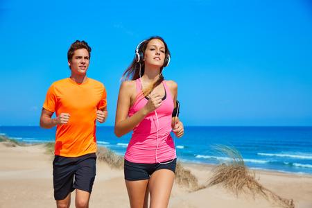 personas corriendo: Pareja joven corriendo en la playa en las vacaciones de verano