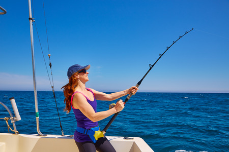 blue sea: Beautiful woman girl fishing rod trolling in saltwater in a boat trolling